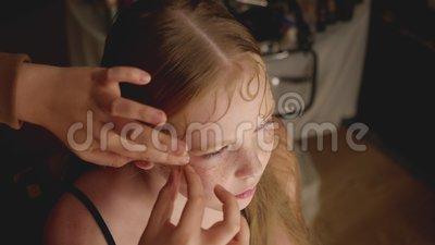 Stylist doing vintage hairstyle to teenage girl. High angle view of stylist doing beautiful retro hairstyle to adorable serious teen girl in beauty salon stock video