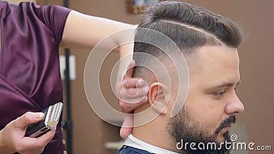 Stylist em roupas vermelhas escuras cortando cabelos de clientes com clipe Homem no salão de cabeleireiro Mestre no trabalho em b video estoque