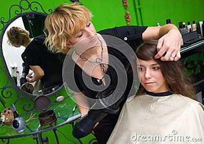 Stylist with hair dryer working