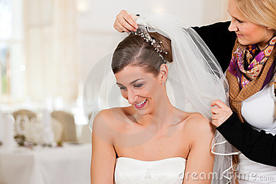 Stylist pinning up a bride s hairstyle
