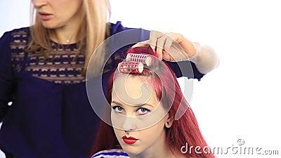 Styliste féminin créant la coiffure parfaite avec de grandes boucles pour la jeune femme rousse
