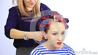 Styliste f?minin cr?ant la coiffure parfaite avec de grandes boucles pour la jeune femme rousse