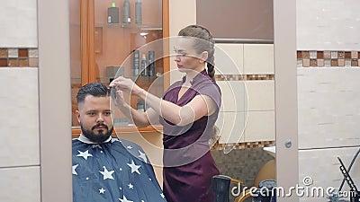 Stylistisches Schneiden männlicher Haare mit Schere und Kamm, mittlerer Schuss Kapitän und Klient, reflektiert im Spiegel, aufgen stock video footage
