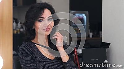 Stylowa piękna kobieta patrząca w lustro prostująca włosy w salonie piękności i uśmiechająca się patrząc na zdjęcie wideo