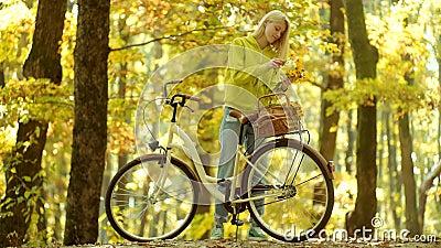 Styre f?r cykel f?r flickaarminnehav gammalt med blommakorgen Den h?rliga unga kvinnan p? cykeln parkerar in carefree kvinna H?st lager videofilmer