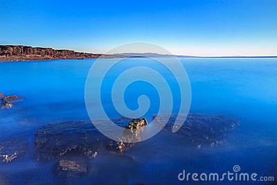 Submerged rocks, blue ocean, clear sky on bay beach sunset