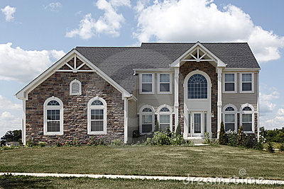 Suburban home with arch and stone garage