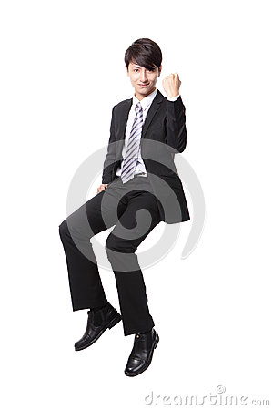 Successful business man sitting on something