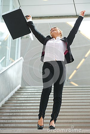 Successful business woman celebrating with arms raised