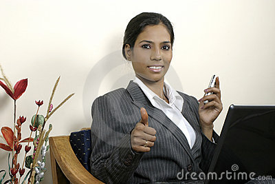 Successful business woman thumbs up with laptop