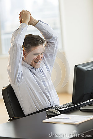 Successful Businessman With Arms Raised Using Computer