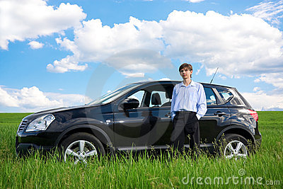 Successful businessman with car on grassland