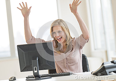 Successful Businesswoman With Arms Raised Looking At Computer