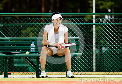 Successful female tennis player rests at the bench
