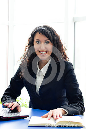 Successful business woman at office workplace with laptop & book