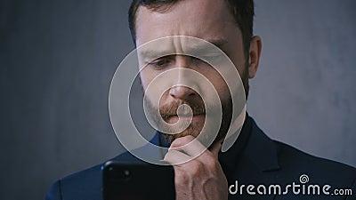 Succesvolle mannelijke ondernemer die op zoek is naar een smartphone die over zaken denkt Serieus begeleide zakenman in het pak d stock footage