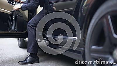 Succesvolle zakenman die van de auto van de premieklasse, aankomst aan werkplaats weggaan stock footage
