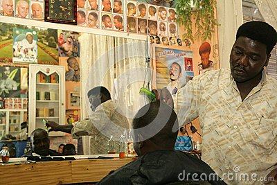 A Sudanese refugee working in a barber shop Editorial Stock Image