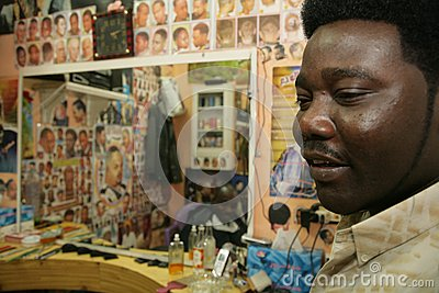 A Sudanese refugee working in a barber shop Editorial Image