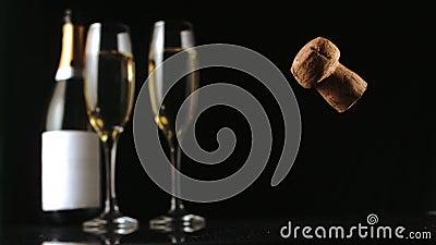 Sughero di Champagne che cade davanti a due flauto e bottiglie di vetro