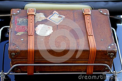 Suitcase in the luggage rack of vintage car before a trip around