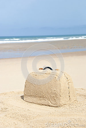 Suitcase made out of sand on beach