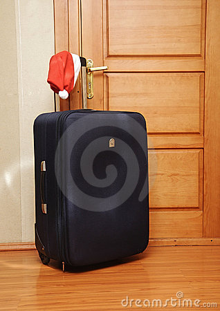 Suitcase and santa hat against a wooden door.