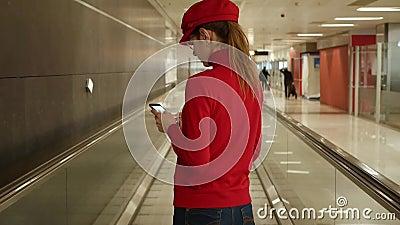 Sul retro, una donna europea con telefono in marcia all'aeroporto internazionale Ragazza con smartphone sul trasportatore passegg archivi video