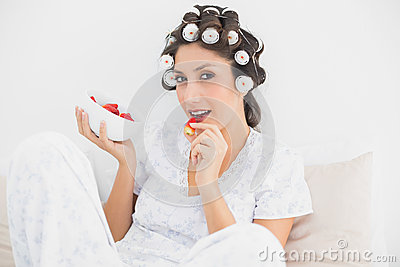 Sultry brunette in hair rollers having a bowl of strawberries