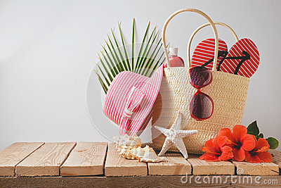 Summer beach bag and hibiscus flowers on wooden table. Summer holiday vacation concept. View from above Stock Photo
