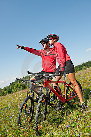 Summer bike - Young sportive couple in meadow