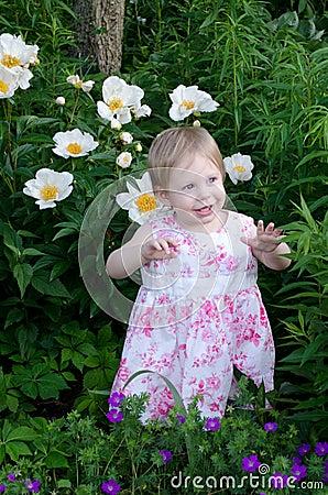 toddler in pink in a garden