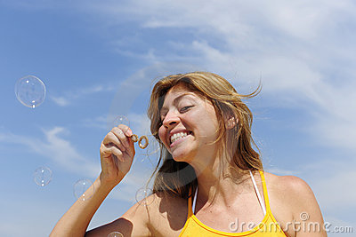 Summer fun: woman blowing soap bubbles outdoors