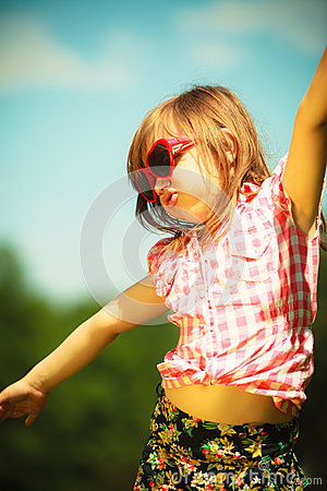 Summer. Girl kid in red sunglasses playing outdoor