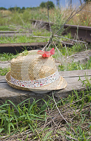 Summer hat and poppy on railway