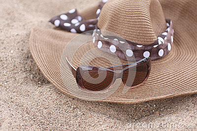 Summer hat and sunglasses on the Sand