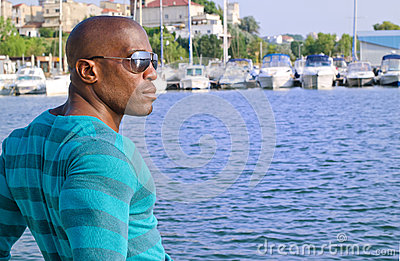 Summer marine scene with a handsome black man relaxing and enjoying the summer.