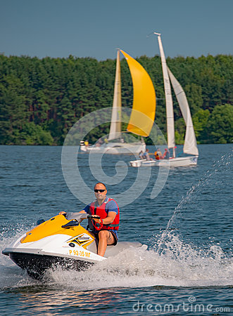 Free Summer Mood: Yellow And White Sails On The Blue Sky Background And A Man On A Yellow Scooter . Stock Photo - 74649220