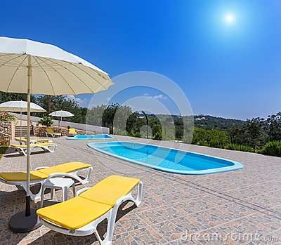 Summer pool with garden and sun loungers.
