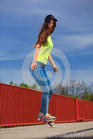 Summer sport. Cool girl skater riding skateboard