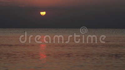 Summer sun behind clouds, above the sea, with gentle reflection stock video