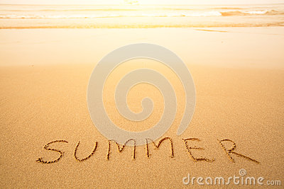 Summer - text written by hand in sand on a beach