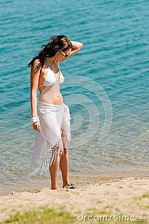 Summer toned woman walking beach in bikini