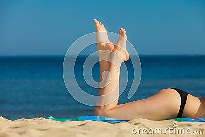 Summer vacation. Legs of sunbathing girl on beach