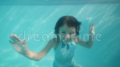 Happy smiling adorable child girl is dancing underwater looking at camera. Summer vacations concept. Portrait of happy smiling adorable child girl is dancing stock video footage