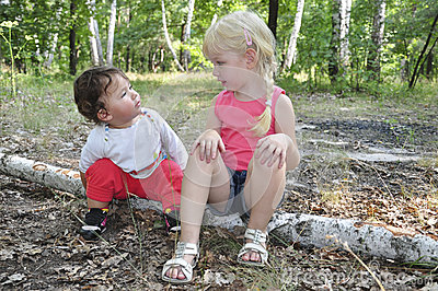Summer in the woods on birch logs sits two little sisters