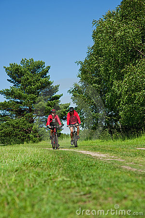 Summer - Young couple riding bike in the nature