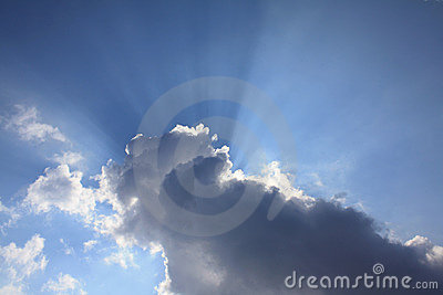 Sun beams behind cloud blue sky