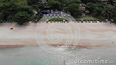 Sun-Betten auf Strand Vogelperspektive vieler zusammengepaßten Sonnenruhesessel mit Regenschirm auf einsamem Strand mit sauberem  stock video