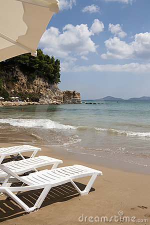 Sun chairs on Alonissos beach against Aegean